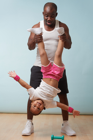 Handsome black young father is holding his cute little daughter upside down at home. She enjoys it big time, swinging from side to side.