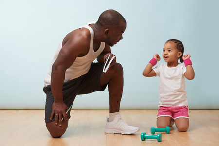 Handsome black young father fitness training his cute little daughter against pale blue background. She happily throws her hands in air victoriously while he commends her performance. Imagens