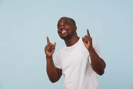 Handsome bold black man in white T-shirt grimacing against pale blue background. looking up, pointing finger up with both hands. Thank you god gesture. Pleased.