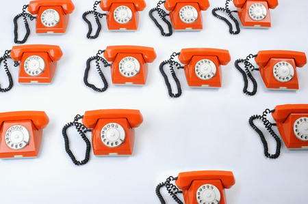Close up of a large group of orange rotary telephones