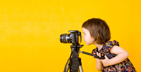 little cute girl holding a digital professional photo camera on tripod.