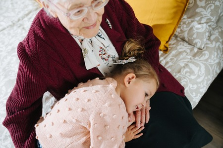 Happy moments with great grandma, senior lady spending quality time with her great granddaughter. Restless naughty little girl taking a nap on her great grandma's knees.