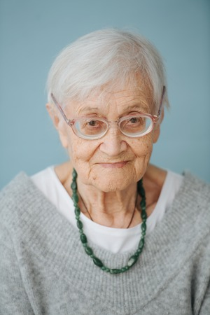 Frontal portrait of elderly grey haired woman wearing comfortable grey V-type sweater at home. Imagens