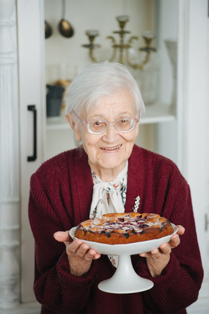 Senior gray haired woman presenting beautiful and tasty holiday pie. Extending it in her arms for the guests to see. Imagens