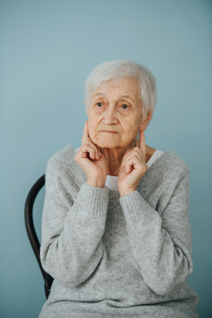 Portrait of elderely grey haired woman in a comfortable sweater at home