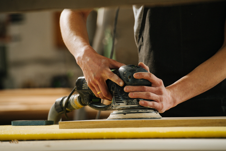 Portrait of working carpenter. He is making furniture on order in a workshop. Smoothing wood panel surface with eccentric grinder. Hands and body only. cropped. Imagens