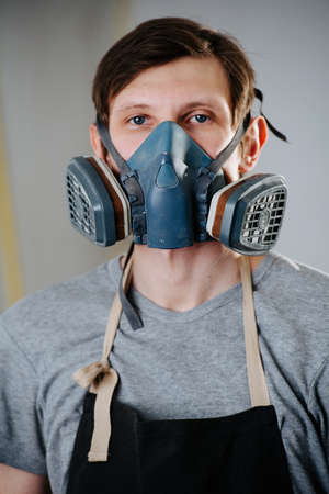 Close up portrait of working handsome slim middle aged brunet carpenter in respirator. He is making furniture on order in a workshop. Standing still for a portrait between worksteps. Painting room.