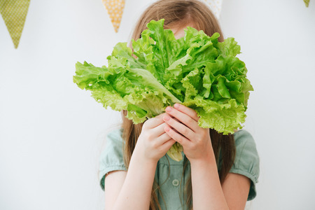 Closeup portrait of  girl covered her face with a green fresh salad Zdjęcie Seryjne - 121248511