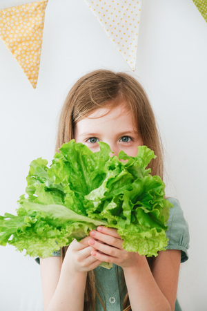 Closeup indoor portrait of girl holding a salad in her hands