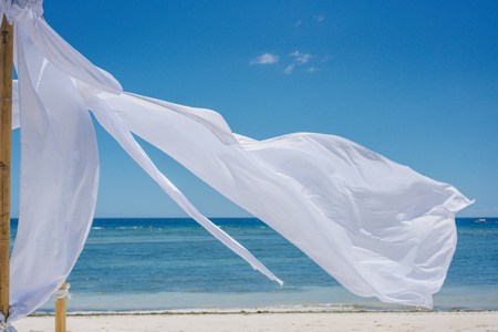Beach shade with white gracefully fluttering fabric curtains on seashore. Sea breeze and white sand. Close up.