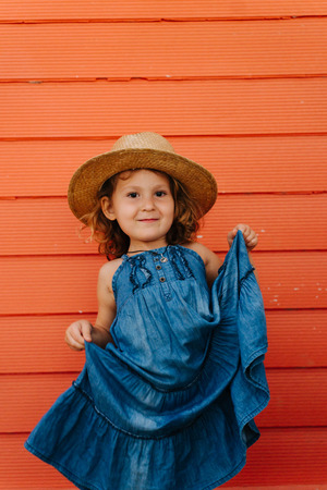Happy child girl in summer hat and a beautiful blue dress against orange wall. Lifting her skirt in a curtsey fashion. Feeling pretty.
