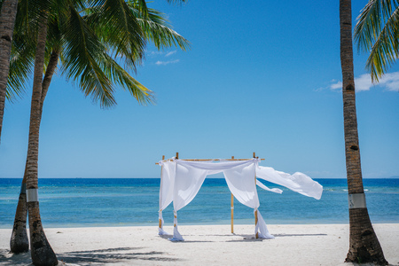 Beach shade with white gracefully fluttering fabric curtains on seashore. Sea breeze, palms and white sand