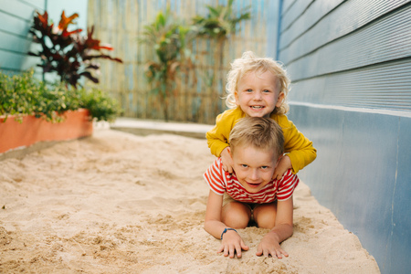 Outdoor summer portrait of two cute happy playing kids, big brother and his little sister against blue house wall. They are riding on each other backs, taking turns. Laughing together.