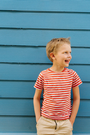 Cute little blond boy in striped T-shirt posing in front of blue house wall. He's posing, looking away, hands in pockets.