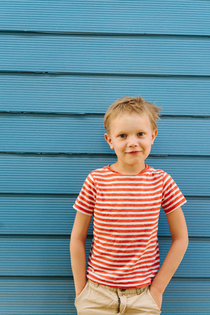 Cute little blond boy in striped T-shirt posing in front of blue house wall. He's posing, making handsome look, hands in pockets. Stock fotó