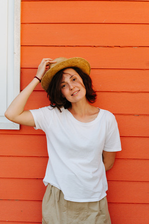 Summer portrait of middleaged brunette woman in white t-shirt smiling with confident expression against orange house wall. Lifting her hat.