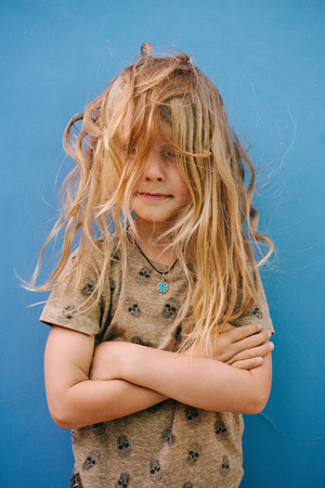 Little boy with long blond hair in white T-shirt posing in front of house wall. His face is completely covered by messy tangled uncombed after swim hair. Hands crossed on chest. Stock Photo