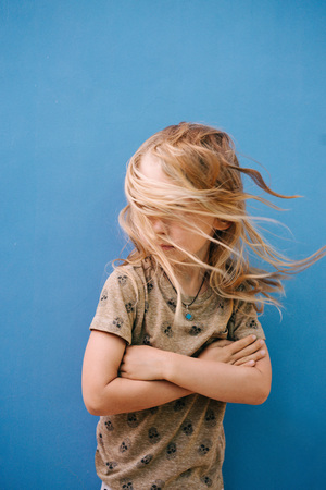 Little boy with long blond hair in white T-shirt posing in front of house wall. His face is completely covered by messy tangled uncombed after swim windy hair. Hands crossed on chest.