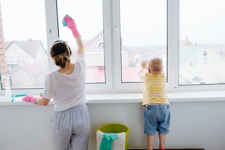 Mother of little blond toddler boy is cleaning plastic window door with wet cloth. He himself is leaving handprints on the next window. Archivio Fotografico