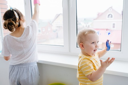 Mother of little blond toddler boy is cleaning plastic window door with wet cloth. He himself has left blue handprints on the next window. Naughty game.