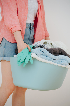 Woman carries a laundry basin full of freshly washed towels. Close up