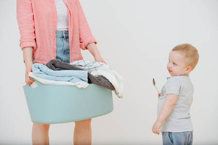 Mother with laundry basin full of washed towels and her blond toddler child with mouth dirty in jam