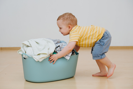 Little blond toddler boy is pushing heavy laundry basin full of washed towels. He's making it slide on the floor