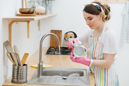 Young happy brunette woman in pink rubber gloves is washing kitchen utensils in a sink.