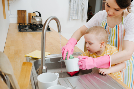 Young happy brunette woman in pink rubber gloves is washing kitchen utensils in a sink. Her toddler son participates