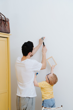 Father and his little toddler son are attaching framed drawings to the wall together. Hammering a nail.