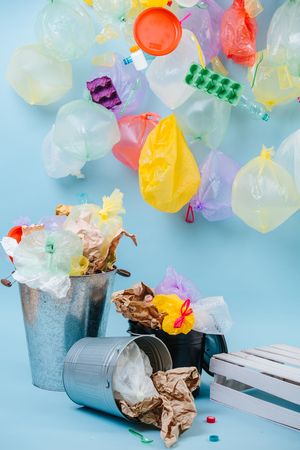 Recycling and ecology. Multi-colored plastic bottles and egg cartons are attached to inflated balloon-like garbage bags. Under it nasty looking trash bins overfilled with recyclable waste.