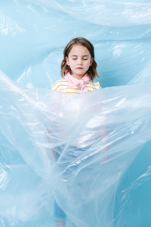 Little brunette girl is wrapped in plastic in protest of waste crisis. She closed her eyes, sinking in figurative plastic whirlpool. Recycling and ecology.
