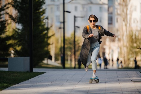 Attractive young woman riding skateboard in a park. She accelerates to high speed.