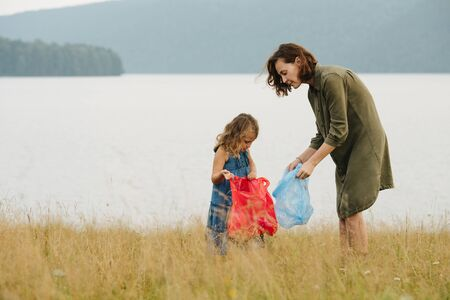 Mother with her preschooler daughter collecting garbage on a meadow next to the river on a cloudy summer day