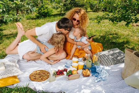 Summer family picnic on grass in gardens under shade of trees. Mother, father, two children sitting on white tablecloth next to their food. Being attentive to small one. Dessert is coming up soon.