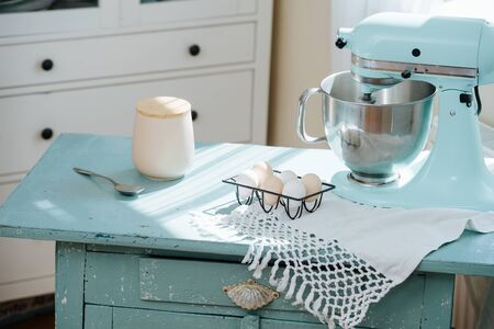 vintage table with a food processor, eggs and crockery for making a cake