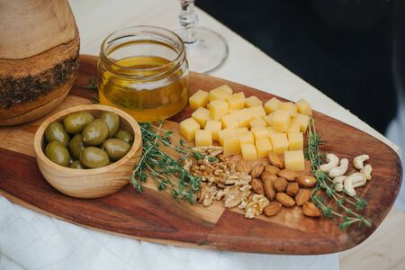 Variety of appetizers for wine such as: olives, cheese, honey, nuts, thyme, served on a wooden plate of a special form. All on a crude plank improvised table, covered with white tablecloth.