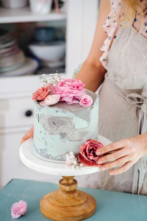 lose-up of a woman's hands and a cake with flowers
