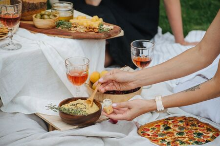 Woman hand scooping hummus with a spoon to smear on bread. Its taken from the wooden bowl. Next to it is wine glass and bowl with cherries, apricots under an appetizer table.