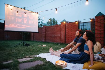 A middle-aged couple in love is watching a movie, in the twilight, outside on the lawn in their courtyard, behind a brick fence. They are sitting on a tablecloth, watching a projector screen.