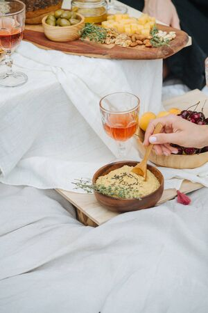 Woman hand scooping hummus with a spoon. Its taken from the wooden bowl with thyme branch lying on its edge. Next to it is wine glass and bowl with cherries, apricots under an appetizer table.