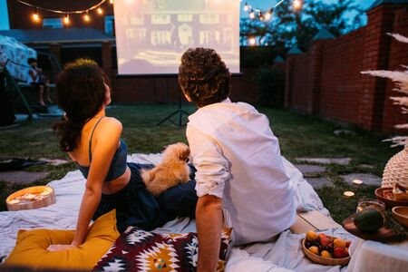 A middle-aged couple in love in the twilight, at the end of the picnic, sitting outside on the lawn in their courtyard. They are watching a movie on a projector screen. Woman holding dog on her knees.