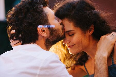 Beautiful middle-aged couple in love is enjoying each other with passion and affection in the evening. Man is gently kissing her in a forehead. Close up. Light in woman's hair.