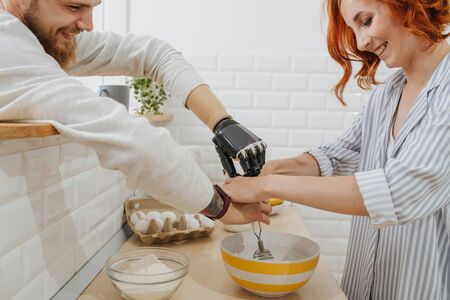 A young man with artificial limb are cooking while standing in the kitchen with his girlfriend, and they laugh. make pancake dough with a bionic hand. closeup of hands