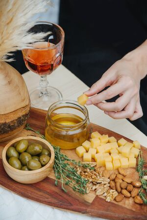 Woman hand dipping cheese cube in honey jar, standing on wooden plate with appetizers, such as: olives, cheese, honey, nuts, thyme. Glass of rose wine is standing next to the plate.