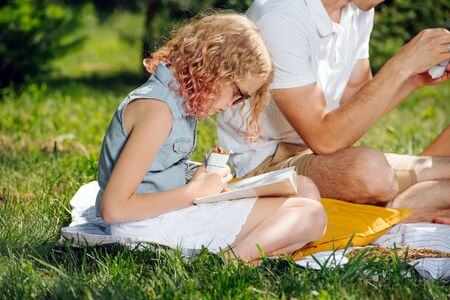 Summer family picnic on grass in gardens under gentle shade of trees. Blonde teenage girl in sunglasses is reading book, and eating sandwich.