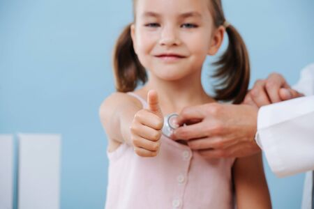 Male doctor hands examining cheerful first grader child girl with two tails by using a stethoscope. Listening to her heartbeat. Blue wall, white objects. She looks straight at camera, shows thumbs up. Standard-Bild - 129110189