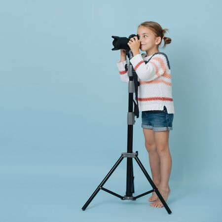 Little girl standing on her toes looking in the camera on tripod, taking picture
