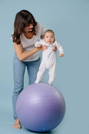 Happy mother carefully and gently doing exercises with her infant child baby on purple yoga ball over blue background. Shes trying to make baby stand on ball, baby is distracted.