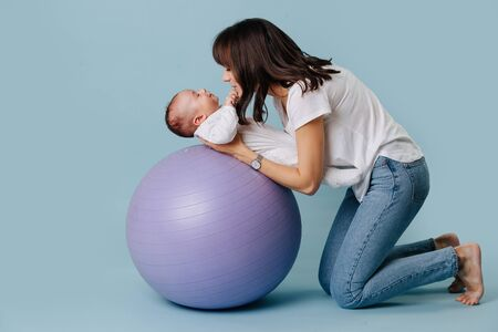 Happy mother carefully and gently doing exercises with her infant child baby on purple yoga ball over blue background. Baby is lying on the back, while they play Their eyes are clothed.